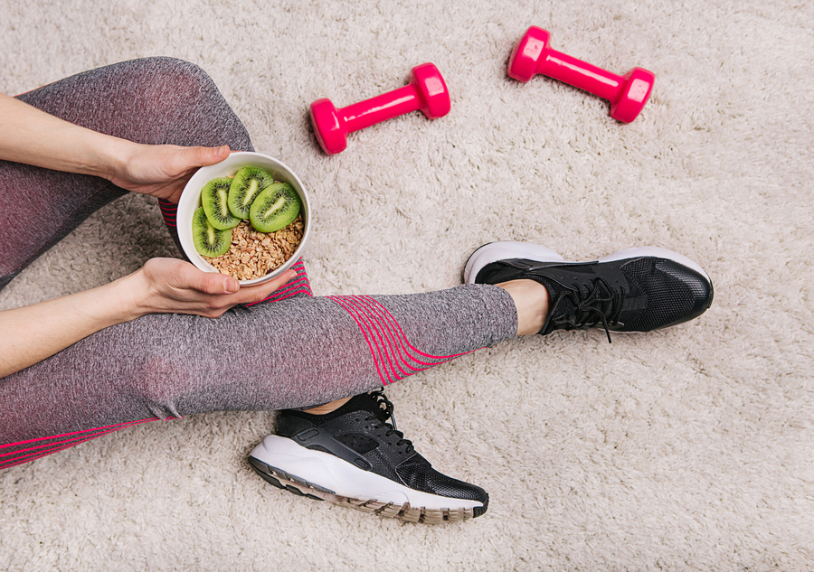 girl-holds-plate-with-muesli-kiwi-after-fitness-workout-with-dumbbells