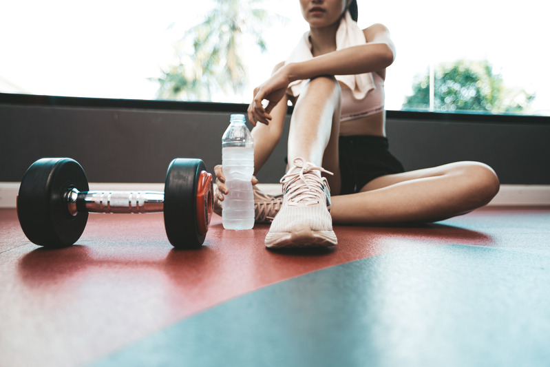 women-sit-back-and-relax-after-exercise-there-is-water-bottle-and-dumbbells
